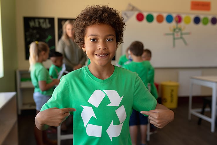 Portrait of an African American schoolgirl with short hair wearing a green t shirt with a white recycling logo on it, pointing at it and looking to camera, smiling in an elementary school classroom, with her classmates and teacher standing in the background